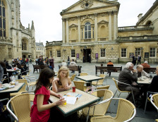 Bath - Two women sitting at a table talking outside Binks Cafe, Abbey Courtyard in the busy city of Bath., Bath, Bath and North East Somerset, England.