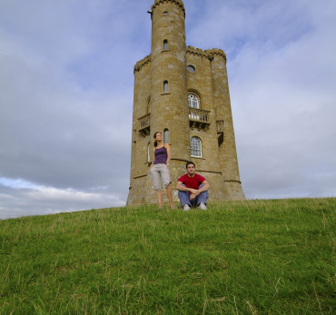 Couple taking in the view from the base of Broadway Tower, a folly built in 1797 at one of the highest points in the Cotwolds, Broadway Tower, Worcestershire, England.