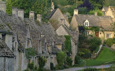 Quaint stone cottages in the Cotswold village of Bibury, Bibury, Gloucestershire, England.