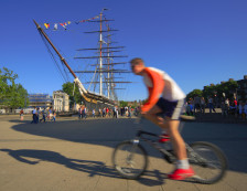 Greenwich, London - Cyclist passing the Cutty Sark. Photo Credit: ©Visit London Images.
