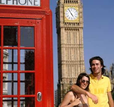 Palace of Westminster - Couple next to a red phone box near Big Ben, enjoying the summer sunshine in England's capital city.