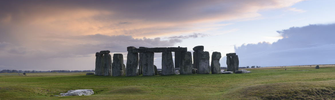 Stonehenge is a pre-historic henge and national landmark on the Wiltshire plain. It is a stone circle of standing stones, with some stones placed horizontally across the top of vertical stones. It is a UNESCO world heritage site. Gathering clouds over the site.