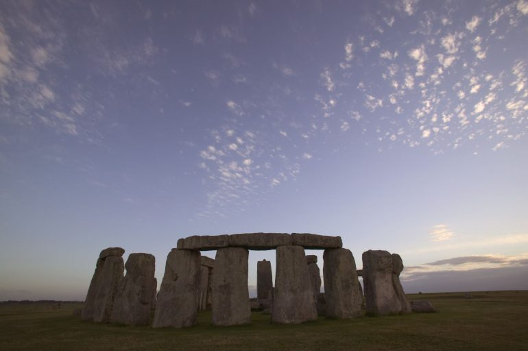 The great and ancient stone circle of Stonehenge, one of the wonders of the world. Stonehenge, Wiltshire, England. Prehistoric henge. Dusk, sunset, sunrise,wispy cloud. Low angle surface view.
