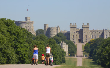 Two mothers with their young children, pushing prams along the Long Walk towards Windsor Castle in the distance. The Long Walk was commenced by Charles II from 1680-1685 by planting a double avenue of elm trees. The central carriage road was added by Queen Anne in 1710. It is a little less than three miles long. To the south of Windsor is The Great Park extending over some 14,000 acres of which 8,000 acres are forest. The public areas are predominantly woodland or open grassland.