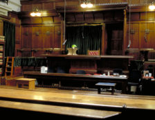 Legal London: London Royal Courts of Justice interior detail of building courtroom, wooden benches, judges chair and table. Photo Credit: ©Visit London Images.