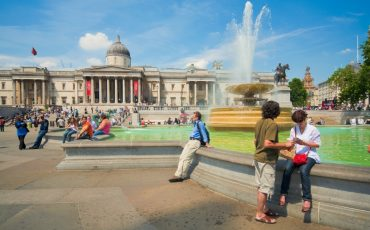 Tourist hanging out in Trafalgar Square with the National Gallery in the backdrop. Photo Credit: ©London & Partners.