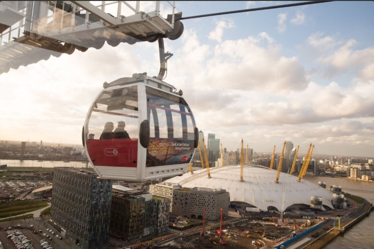 View of Emirates Air Line cabin with O2 in background. Photo Credit: © Emirates Air Line.