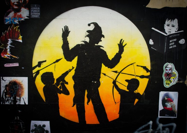 London Street Art: Otto Schade - Children pointing weapons at joker figure. Photo Credit: © Alex Lacey.
