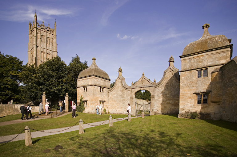 The Cotswolds: People in front of the Gatehouses of Old Campden House, with St James Church in the background. Photo Credit: © James Kerr via Visit England.