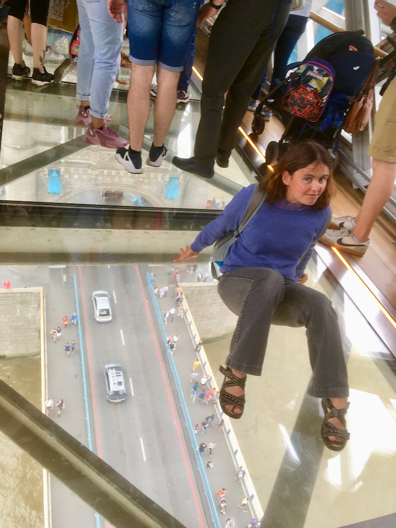 Young lady sitting on glass floor at Tower Bridge in London. Photo Credit: © Edwin Lerner.