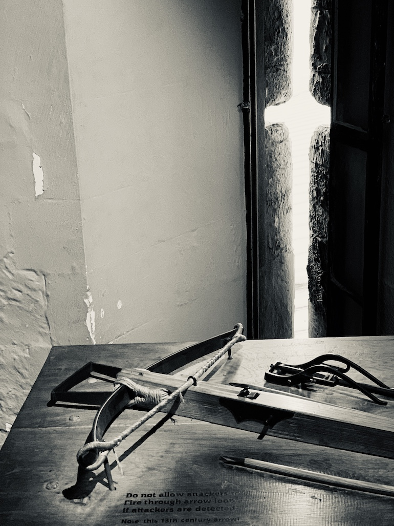 A crossbow rests by an arrow loop window in the Constable Tower at Tower of London. Photo Credit: © Antony Robbins.