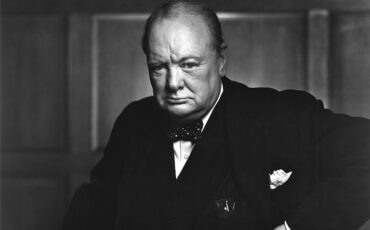 Churchill, aged 67, wearing a suit, standing and holding into the back of a chair. Photo Credit: © Public Domain via Wikimedia Commons.