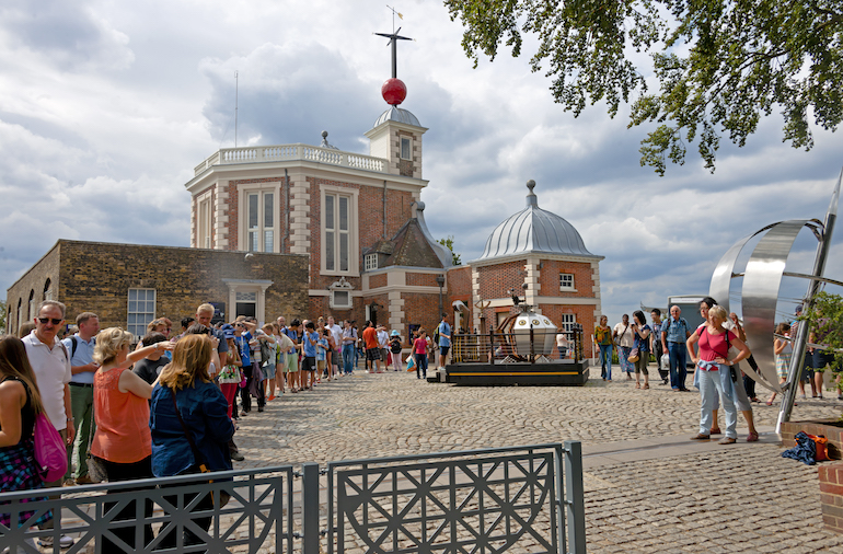 Visitors queuing to take pictures on the line of the Prime Meridian at the Royal Observatory, Greenwich, London. Photo Credit: © Daniel Case via Wikimedia Commons.